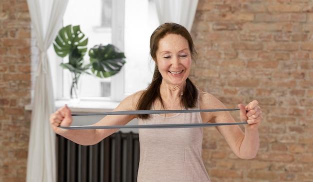 Stretching-band der älteren frau des mittleren schusses