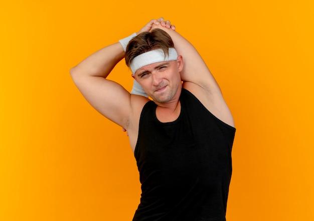 Stretching junger hübscher sportlicher mann, der stirnband und armbänder hält, seinen ellbogen hält und eine andere hand auf den rücken lokalisiert auf orange wand legt