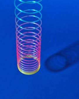 Stretching regenbogen plastik schleichendes spielzeug über blauem hintergrund mit schatten, platz für text.