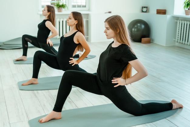 Stretching-training. eine gruppe von jungen mädchen in schwarzen uniformen machen stretching-training im fitnessstudio. akroyoga, yoga, fitness, training.