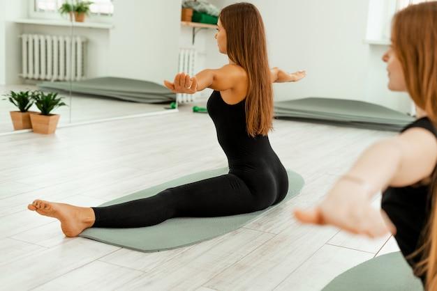 Stretching-training. gesunder lebensstil. junges schönes mädchen in der schwarzen uniform tut, übung ausdehnend. akroyoga, yoga, fitness, training, sport.