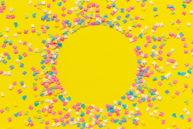Streuen der mehrfarbigen süßigkeitenbelagbehandlung auf gelbem papier. festlicher hintergrund des kreisrahmens