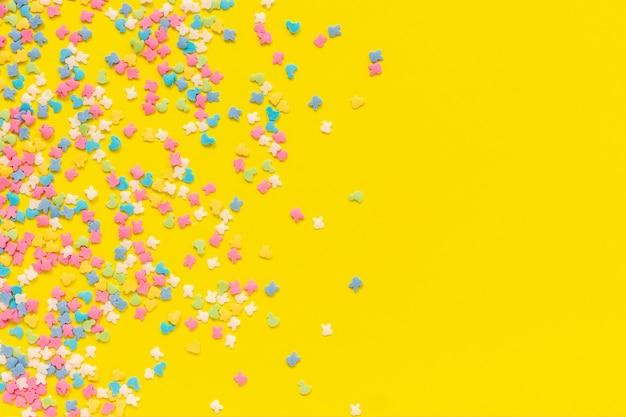 Streuen der mehrfarbigen süßigkeitenbelagbehandlung auf gelbem papier. festlicher hintergrund