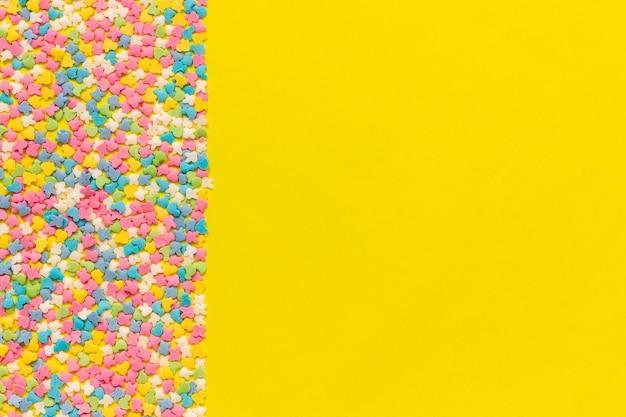 Streuen der mehrfarbigen süßwarenspitze, die auf gelbem papier ankleidet. festlicher hintergrund.