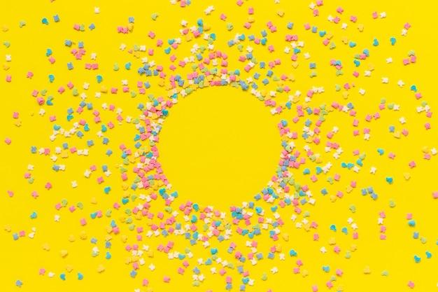 Streuen der mehrfarbigen süßwarenspitze, die auf gelbem papier ankleidet.