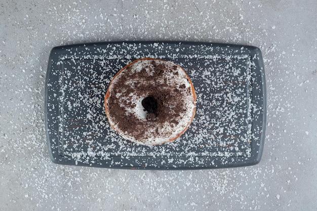 Streuen sie kokosnusspulver um einen donut auf einem tablett auf marmoroberfläche
