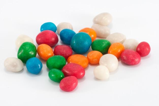 Streuen sie mehrfarbige zuckerglasur-süßigkeiten auf weiß