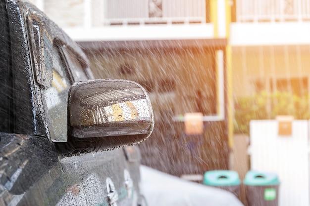 Streuen sie wasser mit einem spray auf das auto, bevor sie das auto mit einer autowaschanlage in der autopflege reinigen.