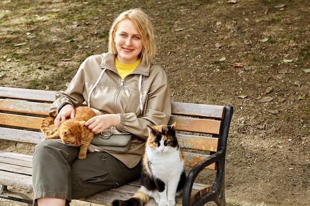 Streunende istanbuler katzen sitzen auf bank nahe lächelnder junger weißer frau.