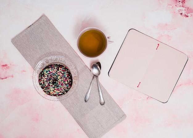 Streusel auf schokoladenkrapfen; kräutertee; löffel und leerer notizblock auf rosa strukturiertem hintergrund