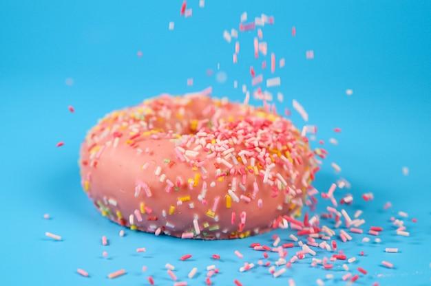 Streusel fallen von oben auf leckeren rosa erdbeerdonut. köstliches dessert auf blauem hintergrund.