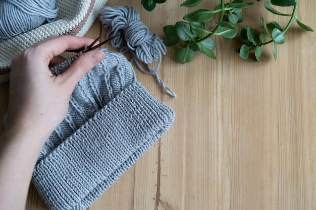 Stricken aus grauem garn in einem dekorativen korb, der auf einem holztablett gehäkelt ist