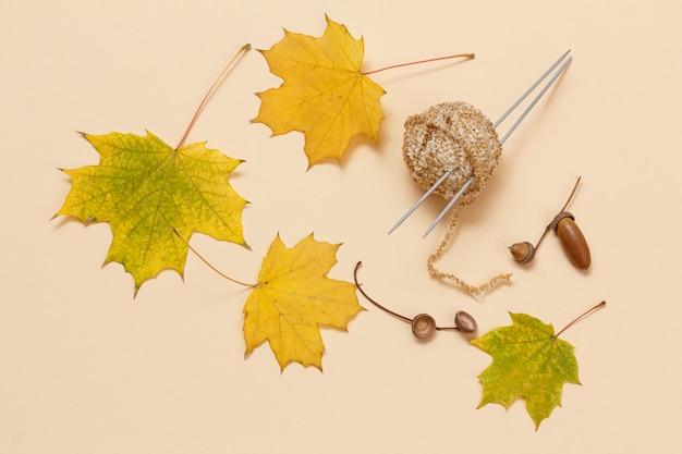 Strickgarnball, trockene ahornblätter und eine eichel auf beigefarbenem hintergrund. strickkonzept. ansicht von oben.