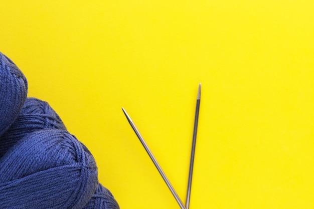Strickgarne in klassischer blauer denimfarbe und metallnadeln auf gelbem hintergrund. knäuel aus wollfäden. handgemachtes und hobbykonzept. flache lage, draufsicht mit kopienraum.