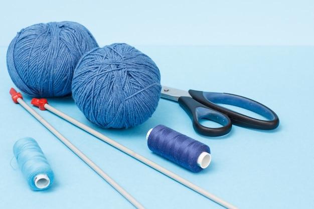 Strickgarnkugeln, metallstricknadeln, fäden und scheren auf blauem hintergrund. strickkonzept.