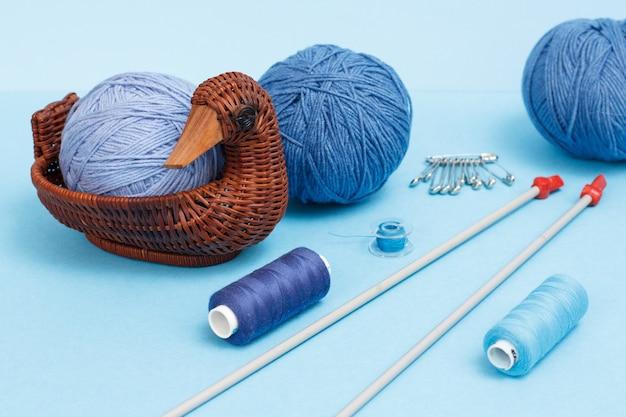 Strickgarnkugeln, metallstricknadeln, fäden und weidenkorb auf blauem grund. strickkonzept.