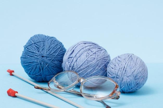 Strickgarnkugeln, metallstricknadeln und brille auf blauem hintergrund. strickkonzept.