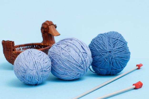 Strickgarnkugeln, metallstricknadeln und weidenkorb auf blauem grund. strickkonzept.