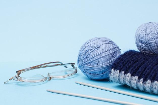 Strickgarnkugeln, schal, metallstricknadeln und brille auf blauem hintergrund. strickkonzept.