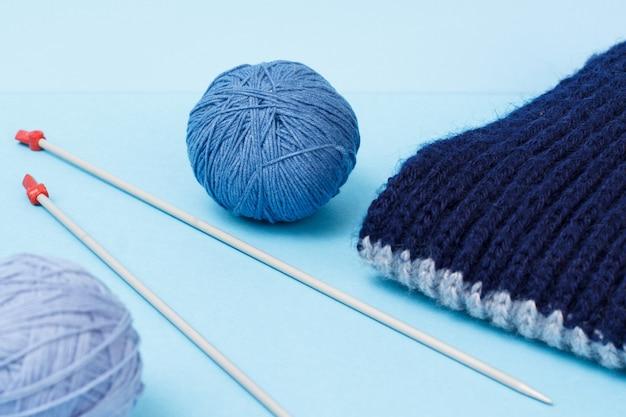 Strickgarnkugeln, schal und metallstricknadeln auf blauem grund. strickkonzept.