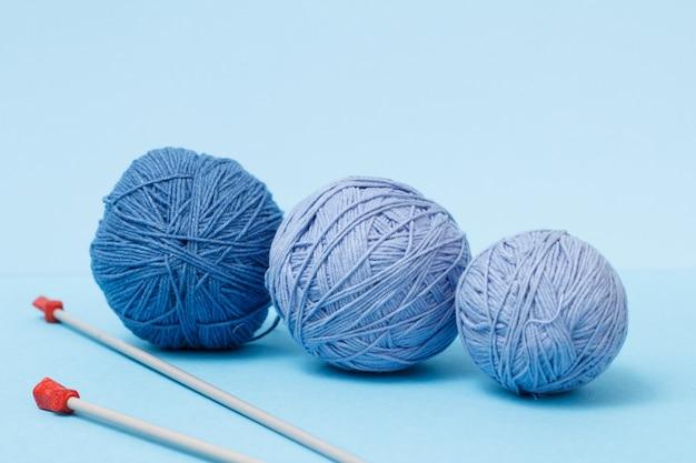 Strickgarnkugeln und metallstricknadeln auf blauem grund. strickkonzept.