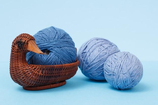 Strickgarnkugeln und weidenkorb auf blauem grund. strickkonzept.