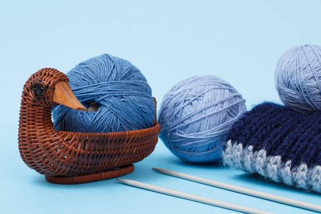 Strickgarnkugeln, weidenkorb, schal und metallstricknadeln auf blauem grund. strickkonzept.