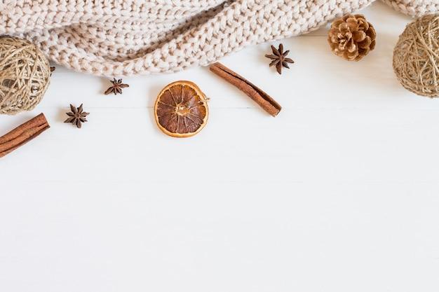 Strickjacken- und weihnachtselemente auf einem weißen hölzernen hintergrund