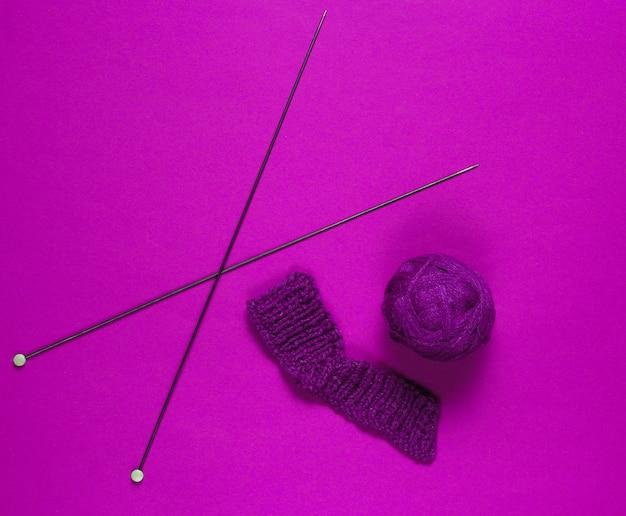 Stricknadeln, fadenkugeln, garn auf rosa hintergrund