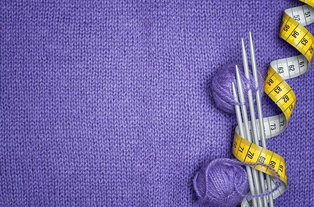 Stricknadeln, gelber zentimeter, wollknäuel auf lila strickware