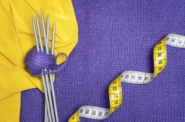 Stricknadeln, gelber zentimeter, wollknäuel, gelber stoff auf lila strickstoff