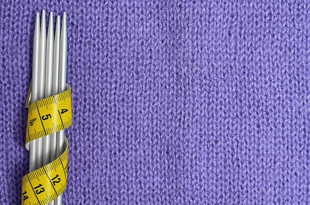 Stricknadeln und ein gelber zentimeter auf einem lila strickstoff