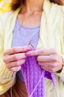 Stricknadeln zum stricken in weiblichen händen sind gestrickte artikel in lila farbe