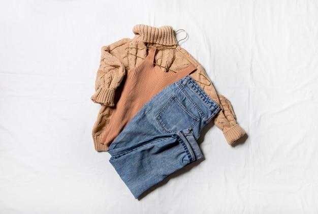 Strickpullover jeans und schuhe auf weißem hintergrund