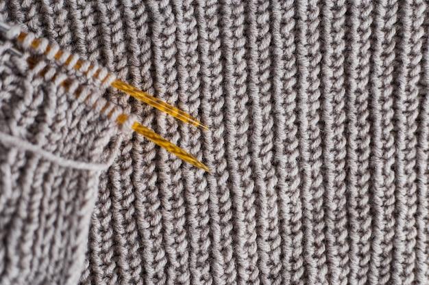 Strickpullover mit stricknadeln. nahaufnahme foto auf grauem hintergrund mit kopienraum. stricken klassenkonzept. hobbys zu hause