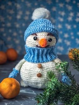 Strickspielzeug weißer schneemann in einem blauen hut mit einem zweig eines weihnachtsbaums und mandarinen
