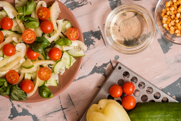 Strömender honigsenf der frau, der in schüssel mit frischem salat auf tabelle ankleidet