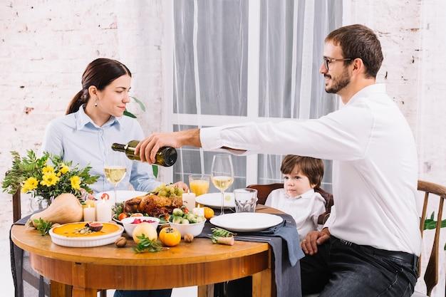 Strömender wein des mannes im glas beim speisen mit familie