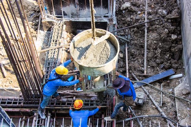 Strömender zement der arbeitskraft, der in gründungsschalung am gebäudebereich in der baustelle gießt.