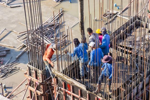 Strömender zement der arbeitskraft, der in grundlagen und in säulenschalungsbereich in der baustelle gießt.