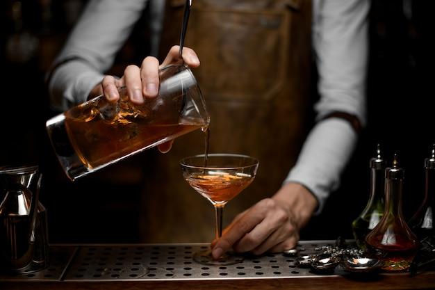 Strömendes alkoholcocktail des barmixers mit einem sieb