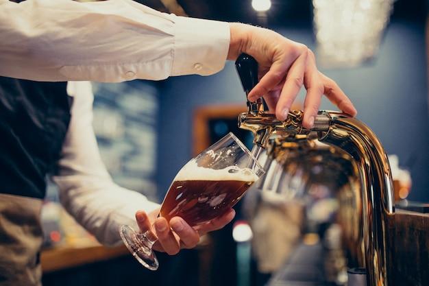 Strömendes bier des männlichen barmixers an einer kneipe