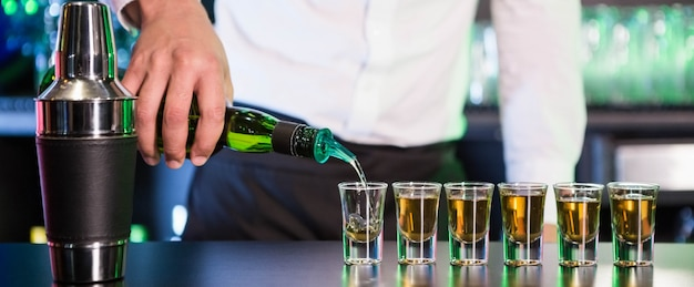 Strömendes cocktail des barmixers in schnapsgläser am barzähler in der bar
