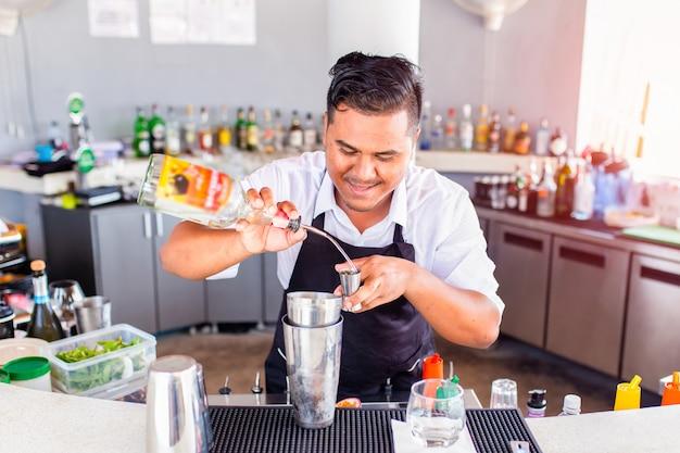 Strömendes cocktail des jungen barmixers in einer bar, phuket, thailand