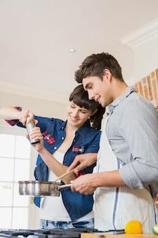 Strömendes salz der frau in gerät während mann, der eine mahlzeit in der küche zubereitet
