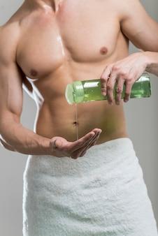 Strömendes shampoo des mittleren schussmannes an hand