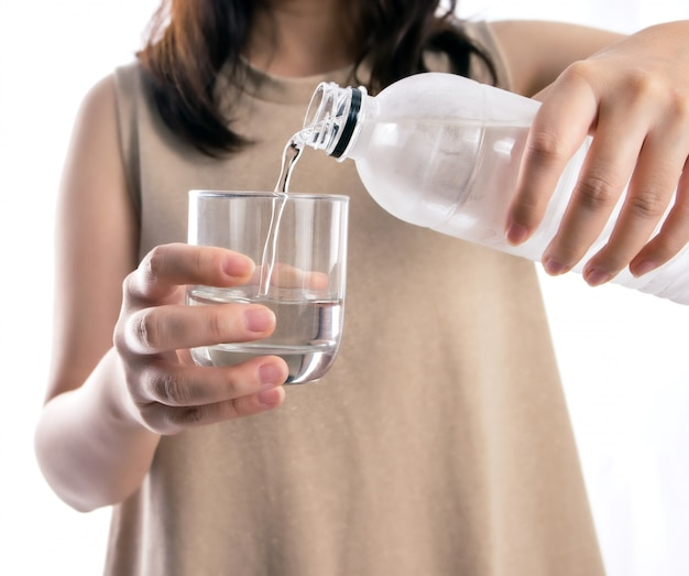 Strömendes wasser der asiatin von einer plastikflasche in ein glas