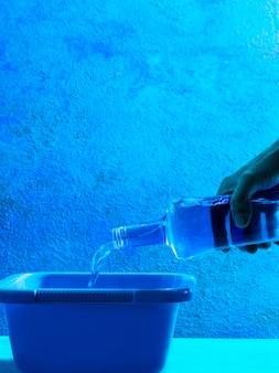 Strömendes wasser der blauen flasche im blauen eimer