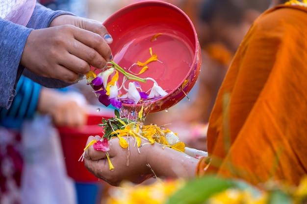 Strömendes wasser der leute zu den buddhistischen mönchen und gibt segen in jährlichem festival thailands songkran im buddhistischen tempel