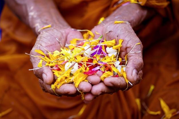 Strömendes wasser der leute zu den buddhistischen mönchen und gibt segen in jährlichem festival thailands songkran